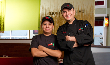 Two confident Chili's Cooks standing in front of a Chili's kitchen