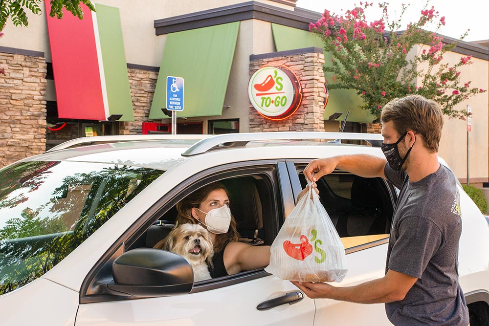 Chili's Team Member with protective mask bringing take-out food to Guest in car)