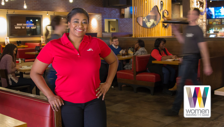 Female Chili's Team Member proudly standing in a Chili's restaurant